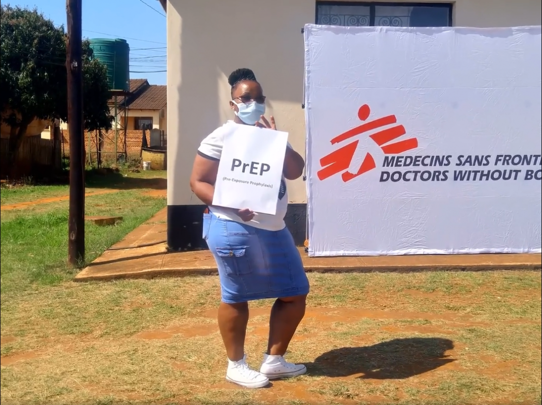 An MSF nurse in Eswatini holds a sign promoting PrEP