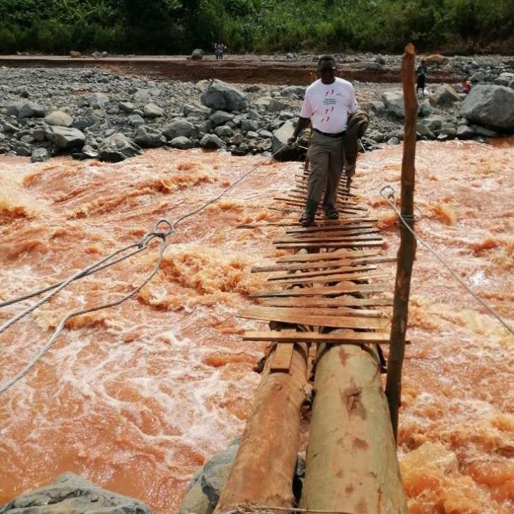 A member of the MSF team crosses the swollen river on the make-shift bridge