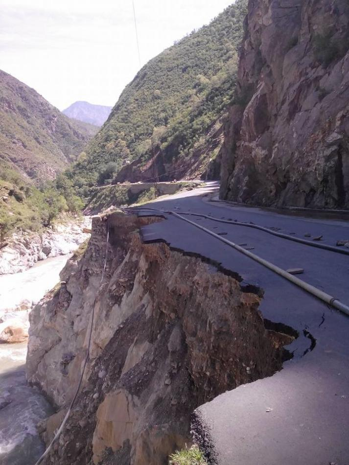 A road has partly fallen away due to damage by the flooding and earthquakes