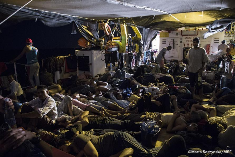 Rescued people try to sleep on the deck of the Dignity 1