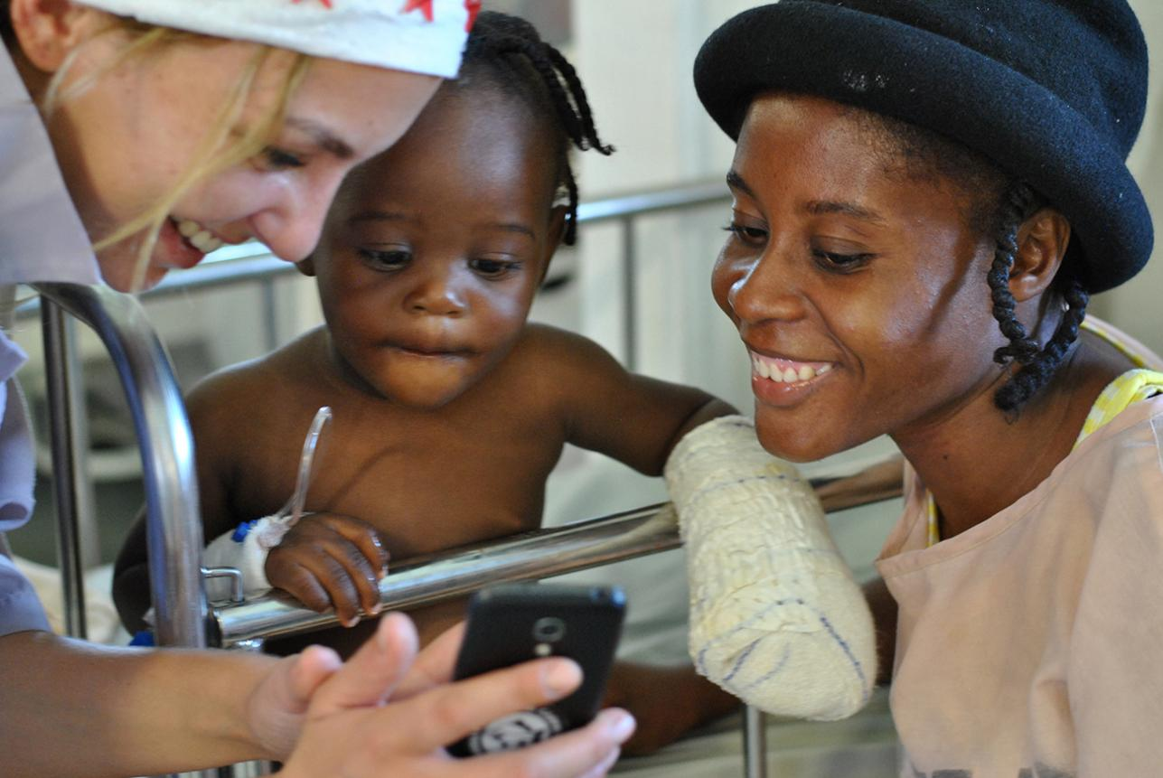 An MSF team member shows her phone to a young patient in Haiti