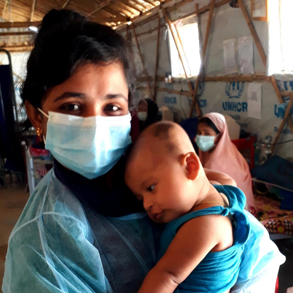 An MSF nurse holds a baby at the MSF hospital in Cox's Bazar