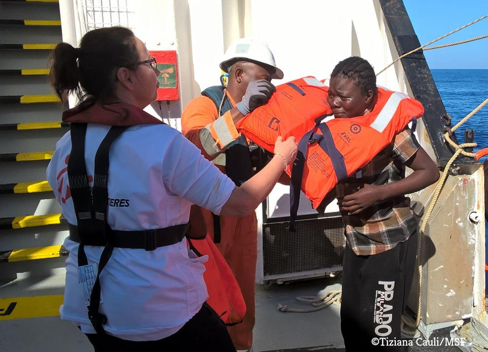 A rescued woman is helped aboard the MSF search and rescue ship