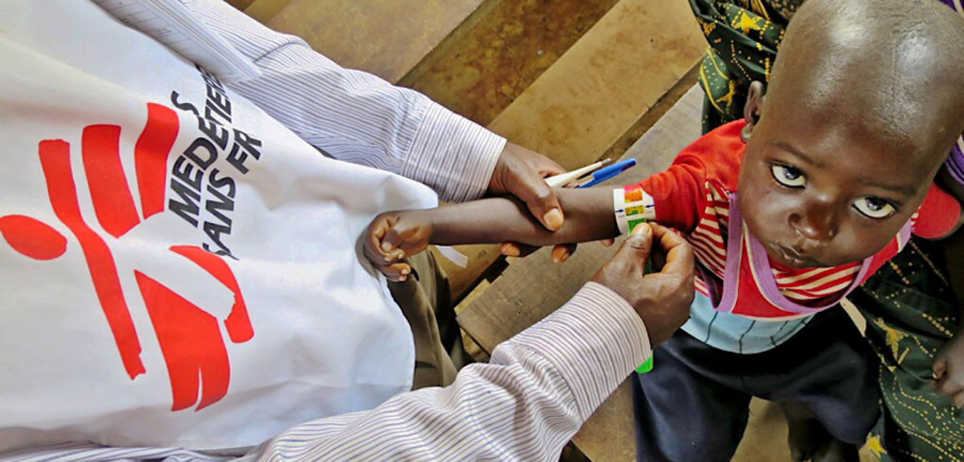 An MSF team member checks a child for malnutrition