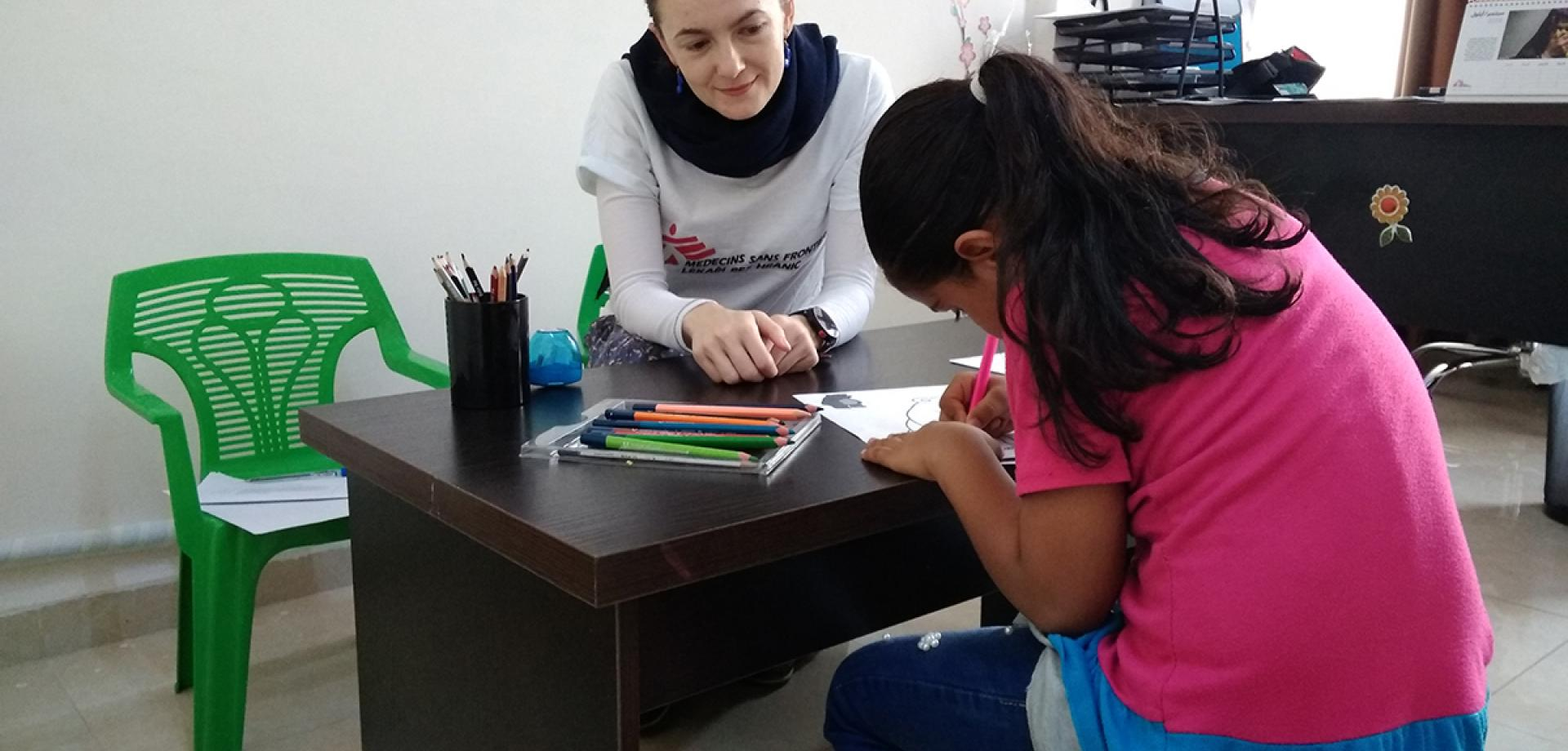 MSF psychologist Kateřina Šrahůlková and a girl draw pictures together