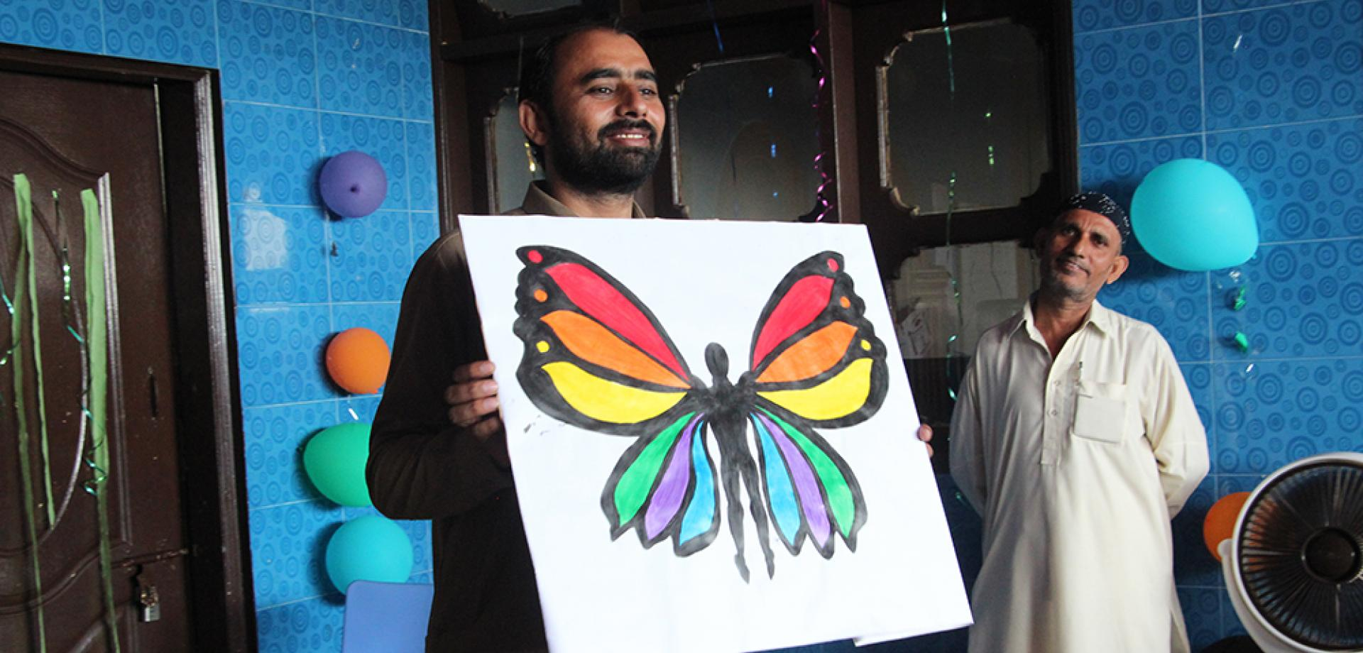 Health Promotion Supervisor Tasawwar Ali discusses the stigma of hepatitis C through the visual representation of a butterfly in Machar Colony, Pakistan.