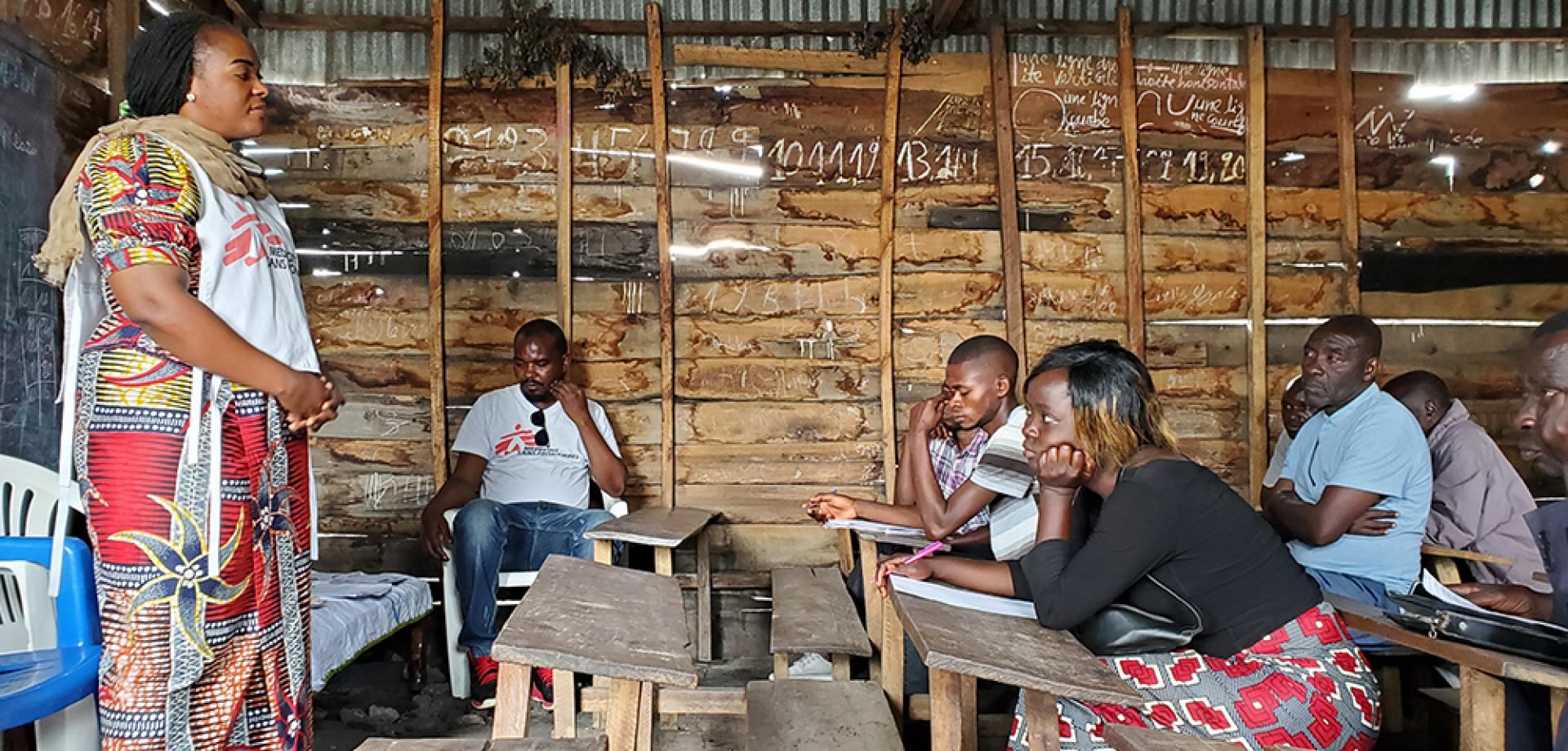 An MSF staff member hosts a COVID-19 health promotion training and information session with a group of volunteer community healthcare workers in the village of Kiziba, North Kivu province, DRC.